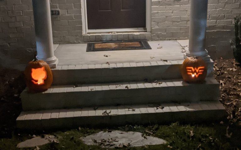 Two pumpkins,lit from within, on a white porch.