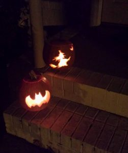 Two carved pumpkins, lit from within with candles, sitting on a front porch stairs.